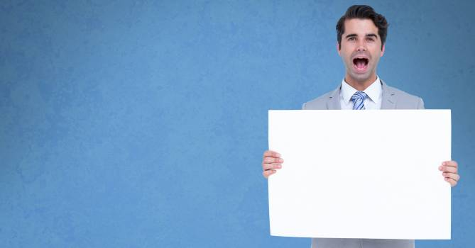 Businessman screaming while holding bill board Free Photo