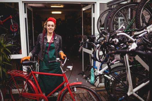 Smiling mechanic standing with a bicycle in workshop #414395