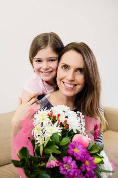 Mother receiving flower bouquet from her daughter Free Photo