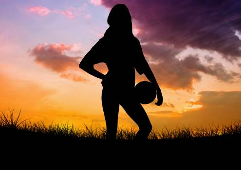 Silhouette of woman holding ball on meadow against sky background #414418