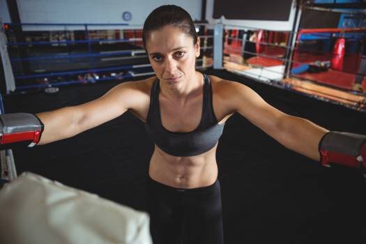 Confident female boxer standing in boxing ring #414433