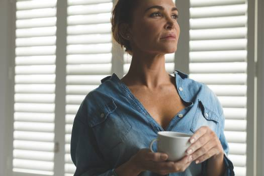 Woman standing in living room while having coffee in a comfortable home Free Photo