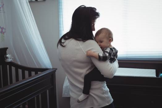 Mother carrying her baby in bedroom Free Photo