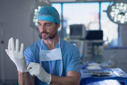 Male surgeon wearing surgical gloves in operation room #414468