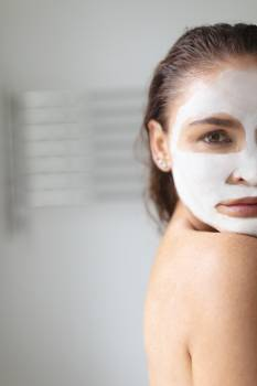 Woman with facial mask standing in bathroom at home #414471