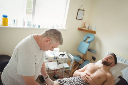 Physiotherapist performing dry needling on the knee of a patient Free Photo