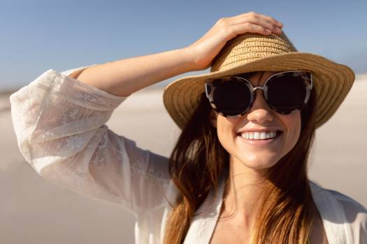 Beautiful woman in hat and sunglasses standing on beach in the sunshine #414494