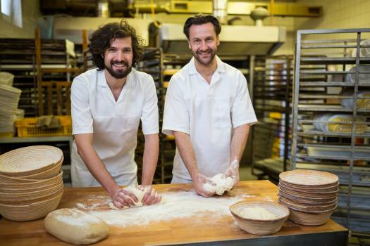 Two smiling bakers kneading dough #414500