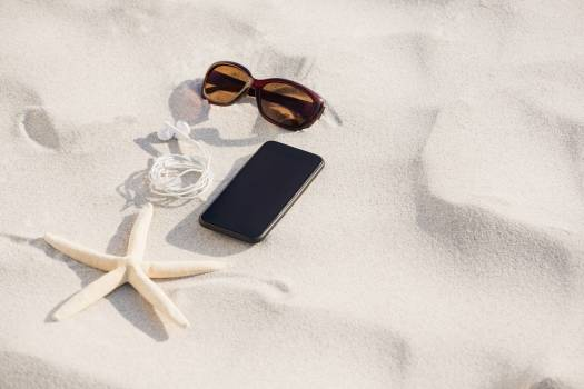 Starfish, sunglasses, headphones and mobile phone kept on sand #414520