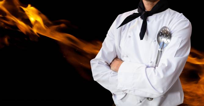 Male chef holding skimmer and standing with flame in background #414530