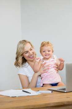 Mother holding baby girl while using laptop #414538