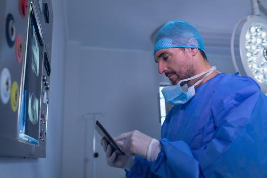 Male surgeon using digital tablet in operating room #414554