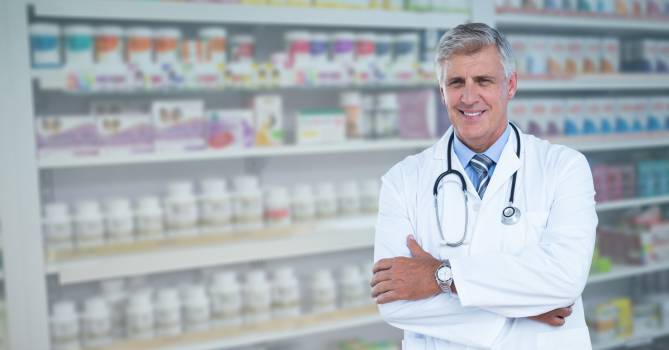 Portrait of confident male doctor standing arms crossed at pharmacy #414578