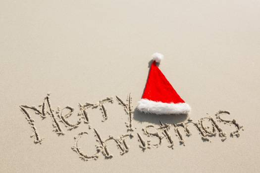 Merry Christmas written on sand with santa hat #414588