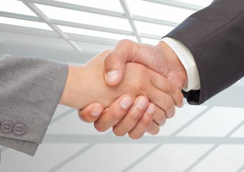 Businessman shaking hands against office in background #414619