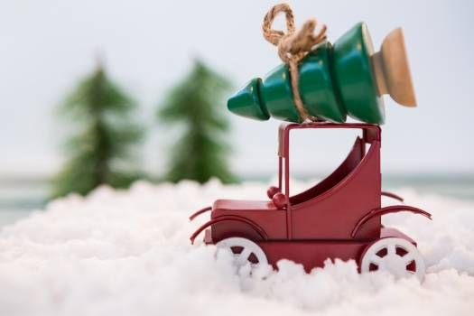 Toy car carrying christmas tree on fake snow #414628