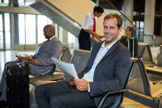 Portrait of businessman reading newspaper in waiting area #414634