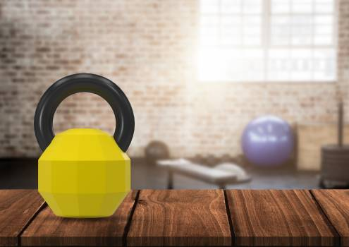 Kettlebell on wooden plank against gym in background Free Photo