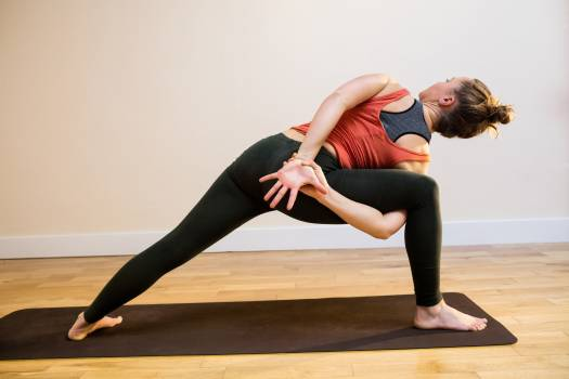 Woman performing bound side angle pose on exercise mat #414694