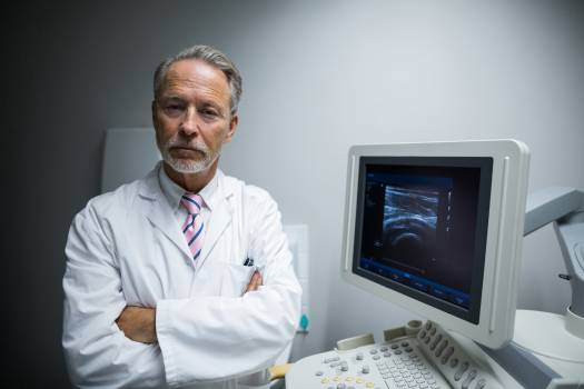 Surgeon with arms crossed standing near ultrasonic device machine #414715