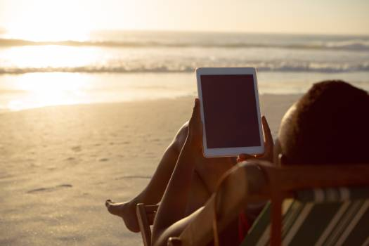 Woman using digital tablet while relaxing in a beach chair on the beach #414757