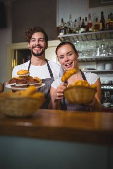 Portrait of waiter and waitress holding cupcakes and bread #414758