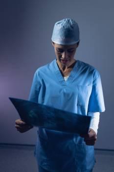 Female surgeon examining x-ray in operating room #414768