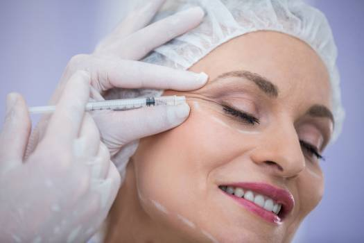 Woman with marked face receiving botox injection #414794
