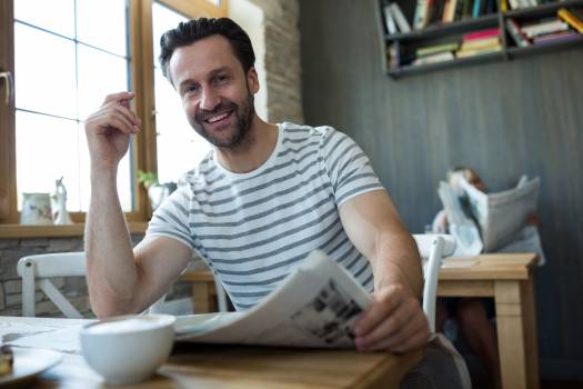 Smiling man sitting with a newspaper in coffee shop #414827