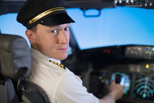 Close up of confident male pilot flying airplane while sitting on seat in cockpit #414838
