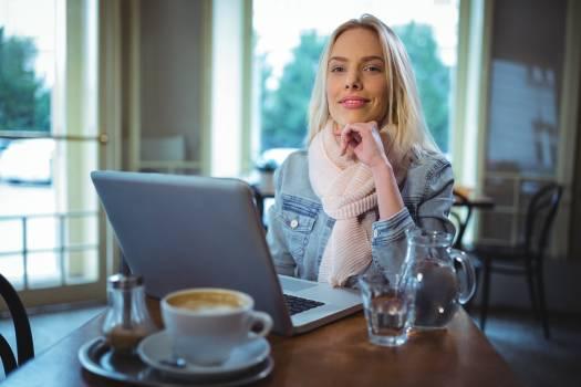Smiling woman using laptop while having coffee #414846