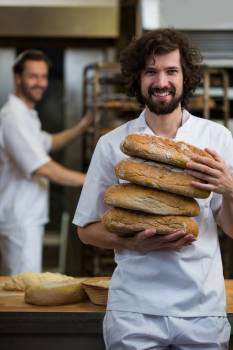 Smiling baker carrying stack of baked breads #414853