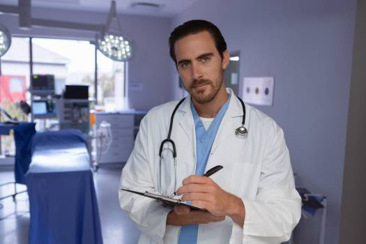 Male doctor writing on clipboard in operation room at hospital #414855