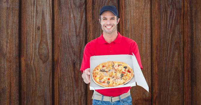 Happy delivery man showing fresh pizza Free Photo