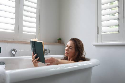 Woman reading a book while relaxing in bathtub at bathroom  #414892