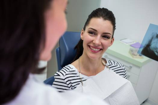 Female patient smiling while talking to doctor Free Photo