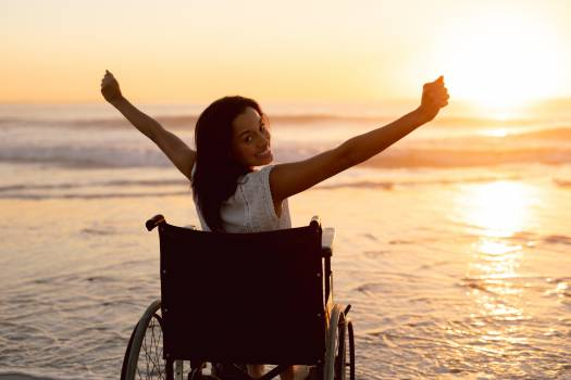 Disabled woman with arms outstretched on the beach #414939