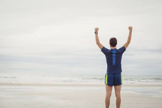 Happy athlete standing on the beach with his hands raised #414952