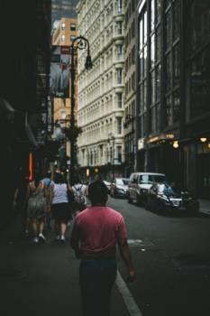 Man In Red T-Shirt Walks Through City #414954