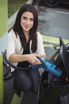 Portrait of beautiful woman charging electric car #415003