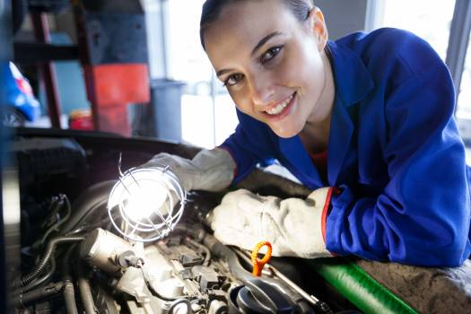Female mechanic examining car engine #415026