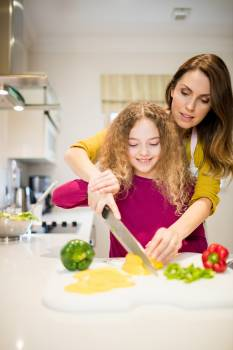 Mother assisting daughter in cutting vegetables in kitchen Free Photo