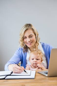 Mother holding baby girl while writing notes in personal organizer #415106