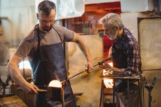 Team of glassblower forming and shaping a molten glass #415113