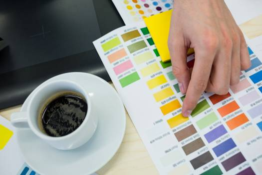 Hands of male graphic designer choosing color from color chart #415154