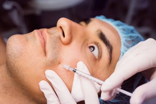 Man receiving botox injection on his face #415216