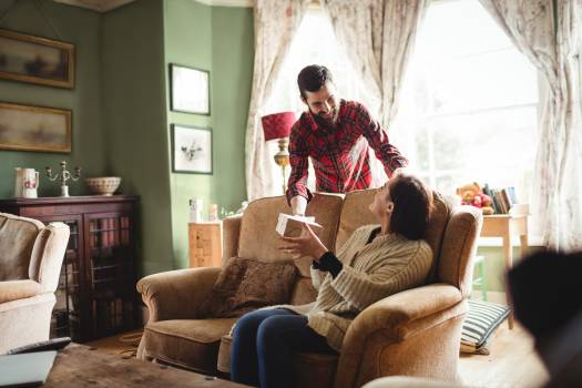 Man surprising woman with a gift in living room #415282
