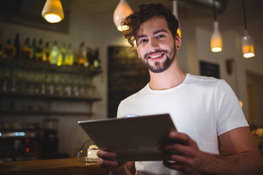 Smiling man using digital tablet in cafe Free Photo