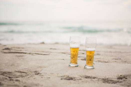 Two beer glasses kept on sand #415426