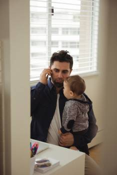 Father talking on mobile phone while holding his baby #415437